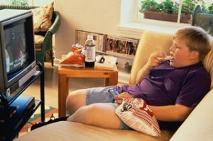 Obese child sitting in front of TV eating junk food